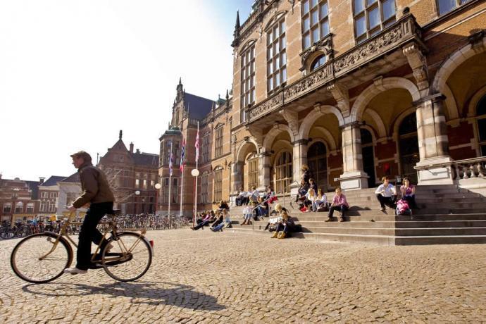 Foto van fietser voor de universiteit van Groningen   credit: University of Groningen